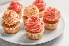 Plate with yummy cupcakes. On wooden table Royalty Free Stock Photos