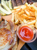 Plateau with assorted grilled pork dishes fries pickles and sauces Royalty Free Stock Photos