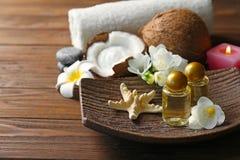 Plateau avec de l'huile de noix de coco en bouteilles, étoiles de mer et fleurs Images stock