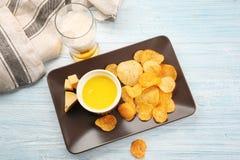 Plateau avec la cuvette de fromage et de pommes chips crémeux photo libre de droits