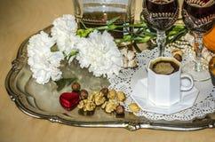Plateau d'argent de nickel avec un bouquet des oeillets, du café noir, des vieux verres cristal et d'une bouteille de boisson alc Photo stock