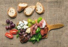 Plateau de fromage et de viande avec des raisins frais, cerise-tomates, oliv Image stock