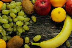 Plateau de fruit des mandarines fraîches, du kiwi, des pommes rouges et des bananes, raisins, sur la table en bois grise Photographie stock