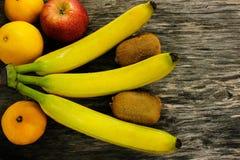 Plateau de fruit des mandarines fraîches, du kiwi, des pommes rouges et des bananes sur la table en bois grise Photos stock