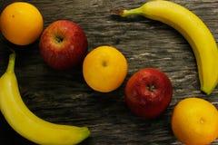 Plateau de fruit des mandarines fraîches et les pommes et les bananes rouges sur la table en bois grise Photographie stock libre de droits