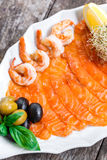 Plateau de fruits de mer avec la tranche saumonée et la crevette, décorées des olives et du citron sur le fond en bois Photographie stock