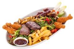 Plateau des viandes, de salade et des pommes frites mélangées Images stock
