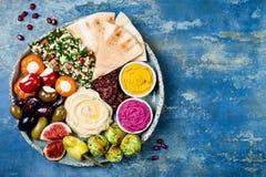 Plateau du Moyen-Orient de meze avec le falafel vert, pain pita, tomates séchées au soleil, potiron, houmous de betterave, olives Photo stock