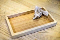 Plateau en bois fait main avec le papier chiffonné sur la table brune Photo libre de droits