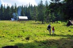 Plateau en bos in bergen, hut, lopende vader en dochter Stock Foto