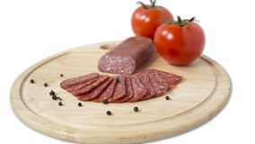 Plate of flat sausage. Plateau chopped flat sausage,black pepper and tomatoes Royalty Free Stock Photo
