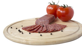 Plate of flat sausage. Plateau chopped flat sausage,black pepper and tomatoes Stock Photos