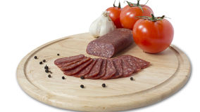 Plate of flat sausage. Plateau chopped flat sausage,black pepper and tomatoes,garlic Stock Images