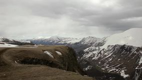 On the plateau view, valley and snow-covered mountains in the background of thick dark clouds. stock video footage
