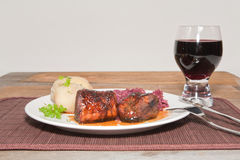 A Plated Broiled Pork Tenderloin with a Shiraz. A studio front view of broiled pork tenderloin glazed with a rum and apple cider reduction served with steamed Stock Image