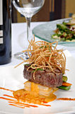 Plated Filet Mignon. Grilled Filet Mignon over scalloped potatoes au gratin, topped with deep fried onions.  There is a wine glass, wine bottle and salad in the Stock Image
