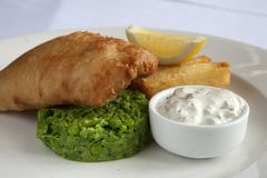 Plated fish and chips with mushy peas. A plate of fish and chips with mushy peas, tartare sauce and a lemon wedge royalty free stock image