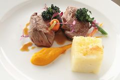 Plated meat meal. Gourmet beef lamb steak plated meal Royalty Free Stock Images