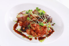 Plated pork and duck confit main meal. Plated pork and duck confit with beans main meal Royalty Free Stock Image