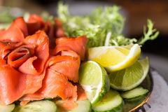 Plated smoked salmon accompanied by lime and lemon wedges. stock photo