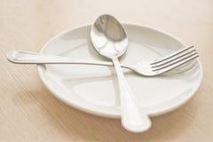 Platee el aislante con la cuchara y la bifurcación en una tabla de madera (Foco en Imagen de archivo