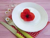 Platee la margarita roja de la flor de la amapola, cuchillo de la bifurcación en un fondo de madera del rosa del restaurante Imagenes de archivo