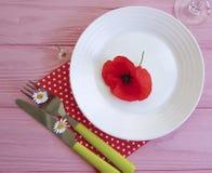 Platee la margarita roja hermosa, cuchillo de la flor de la amapola de la bifurcación en un fondo de madera del rosa del restaura Foto de archivo