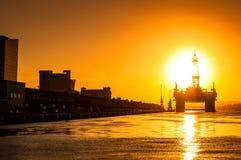 Plateforme pétrolière dans la baie par coucher du soleil photos stock