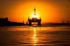 Plateforme pétrolière dans la baie par coucher du soleil photos libres de droits