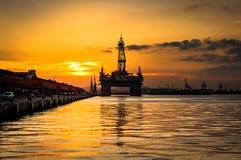 Plateforme pétrolière dans la baie par coucher du soleil photo stock