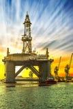 Plateforme pétrolière dans le temps de coucher du soleil photos stock