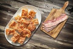 Plateful των φετών πιτών τυριών Gibanica και του τέμνοντος πίνακα με τις φέτες από χοιρομέρι μπέϊκον χοιρινού κρέατος που τίθεντα Στοκ Εικόνα