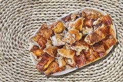 Plateful ψημένων των οβελός φετών χοιρινού κρέατος που τίθενται στο τραχύ αγροτικό υφαμένο Raffia χαλί θέσεων Στοκ Εικόνες