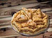 Plateful ленивых кусков яблочного пирога установленных на завязанную таблицу сада древесины сосны Стоковое Изображение RF
