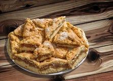Plateful ленивых кусков яблочного пирога установленных на завязанную таблицу сада древесины сосны Стоковая Фотография