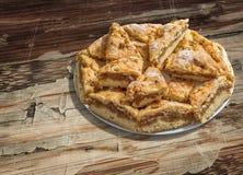 Plateful ленивых кусков яблочного пирога установленных на старую треснутую облупленную деревянную таблицу сада Стоковое Изображение RF