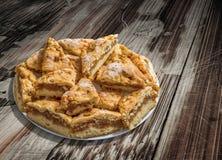 Plateful ленивых кусков яблочного пирога установленных на старую треснутую облупленную деревенскую деревянную таблицу сада Стоковое Фото