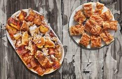 Plateful зажаренного в духовке вертелом мяса свинины и скомканных кусков пирога сыра установленных на старую выдержанную облуплен Стоковые Фото