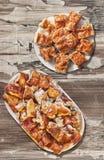 Plateful зажаренного в духовке вертелом мяса свинины и скомканных кусков пирога сыра установленных на старую выдержанную облуплен Стоковое Фото