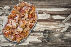 Plateful зажаренных в духовке вертелом кусков мяса свинины установленных на старую отлакированную треснутую облупленную деревянну Стоковые Изображения RF