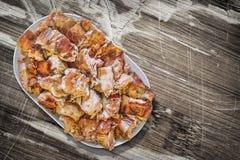 Plateful зажаренных в духовке вертелом кусков мяса свинины установленных на старую отлакированную треснутую, который слезли дерев Стоковые Изображения RF