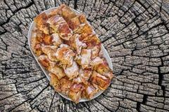 Plateful зажаренных в духовке вертелом кусков мяса свинины установленных на старый выдержанный треснутый стол для пикника пня Стоковое Изображение RF