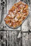 Plateful зажаренных в духовке вертелом кусков мяса свинины установленных на старую выдержанную треснутую деревянную таблицу сада Стоковые Изображения RF