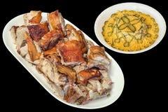 Plateful зажаренных в духовке вертелом кусков свинины с салатом Olivier в белом шаре фарфора изолированном на черной предпосылке Стоковые Изображения
