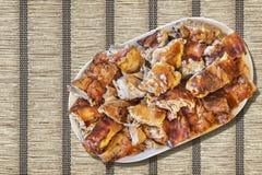 Plateful зажаренных в духовке вертелом кусков свинины установленных на переплетенную Ocher бумажную поверхность Grunge циновки ме Стоковое фото RF