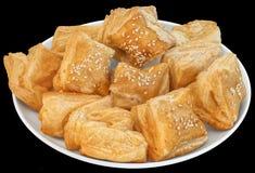 Plateful малого квадратного печенья слойки Zu-Zu сезама изолированного на черной предпосылке Стоковая Фотография RF