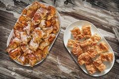 Plateful пирога Gibanica сыра и зажаренных в духовке вертелом кусков мяса свинины установленных на старую таблицу сада Стоковая Фотография