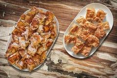 Plateful пирога Gibanica сыра и зажаренных в духовке вертелом кусков мяса свинины установленных на старую таблицу сада Стоковая Фотография RF