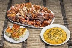 Plateful свинины зажаренного в духовке вертелом с русским хлебом салата и багета объединенным с хлебцами хлеба пита на циновке ме Стоковая Фотография