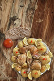 Plateful Of Oven Baked Lemon Chicken Meat With Seasoned Potato Halves And Tomato Set Alongside On Old Cracked Garden Table Stock Photography